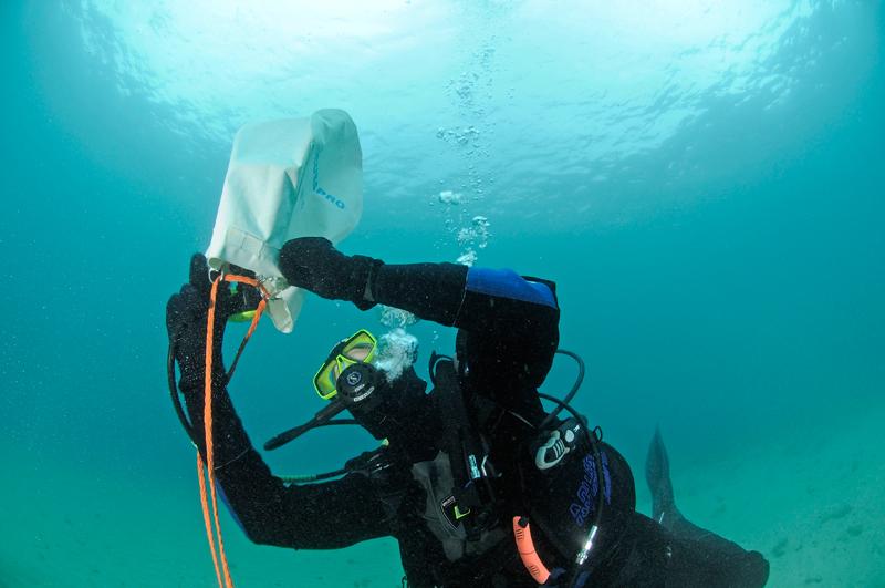 Danach benutzt Roland seinen Oktopus, um den Hebesack zu füllen. Er verwendet dabei nur gerade so viel Luft, dass der Hebesack senkrecht im Wasser vor den beiden Tauchern stehen bleibt.