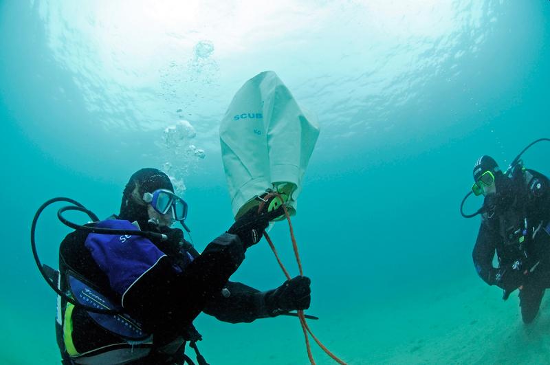 Sandra zieht ihren Oktopus, hält ihn in die Öffnung des Hebesacks und drückt die Luftdusche. Der erst wenig gefüllte Hebesack dehnt sich aus und beginnt in Richtung Oberfläche aufzusteigen.