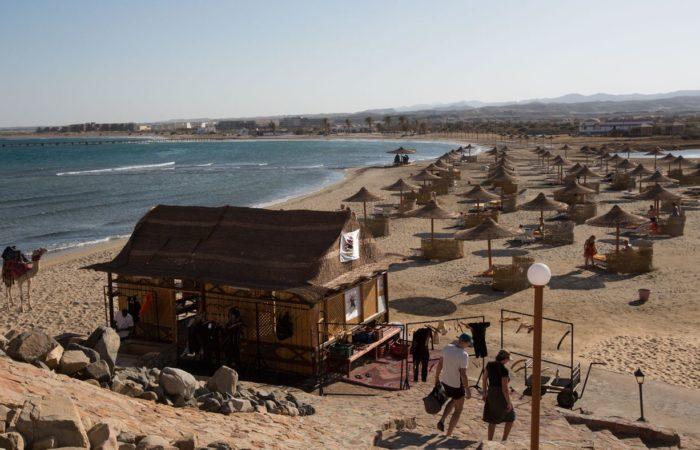 Alles da: Vom Grillrestaurant blickt man einen Hügel hinunter auf einen weiten Strand mit Sonnenschirmen, Strandliegen, dem obligatorischen »Kamel zum Anfassen«, und, last but not least, dem Trockenraum der Tauchbasis.